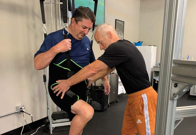 Monty is working with Mike to build strength in his leg while unweighted.